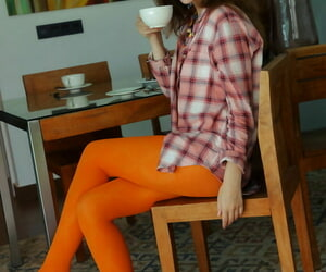 Young redhead Sienna removes orange tights on her way to getting totally naked