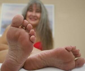 Full-grown MILF Leilani Lei flaunts her oiled feet debilitating red underwear on a bed