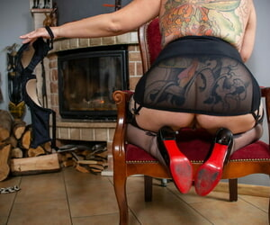 Thick older lady removes well worn heels to show the soles of nylon clad feet