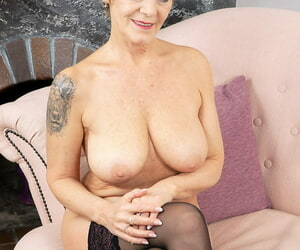Beamy titted older lady Nicol Mandorla sucks on a sextoy while enervating stockings