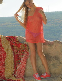 Nice teen girl Linda takes off see thru clothes to pose nude in the hills