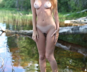 Young blonde girl wanders into a watery marsh with no clothes on