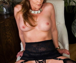 Classy mature woman Holly Kiss strips to nylons and garters