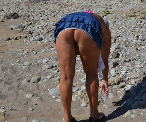 Hugely busty mature slut Chrissy swims and lounges at the beach stark naked