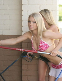 Blonde girl and her girlfriend wash a truck at the car wash in skimpy bikinis