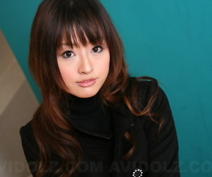 Japanese girl with a pretty face models non nude in a black coat and jeans