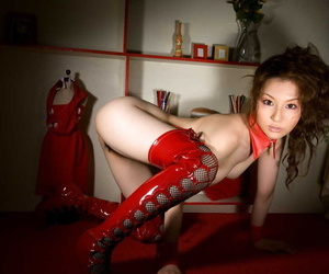 Young Japanese girl Tatsumi Yui strikes great poses in red latex OTK boots