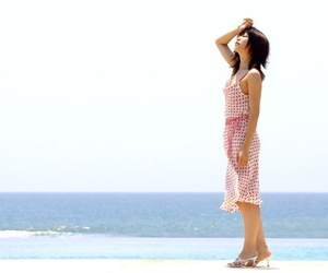 Young looking Japanese girl Saki Ninomiya gets naked with ocean behind her