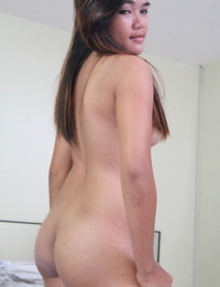 Young Filipina girl with a saucy look stands naked after undressing