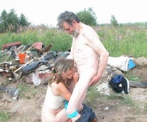 Horny mature lady seduces and fucks a homeless man amid his trash heap