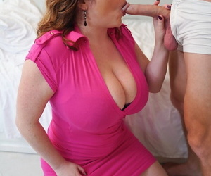 Busty older redhead Maggie Green seduces a younger boy in a tight pink dress