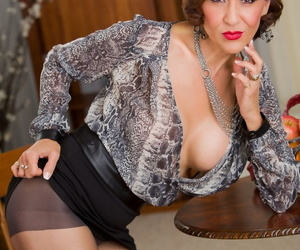 Classy older lady Roni Ford slowly undresses in mini skirt and nylons