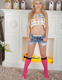 Young looking blonde Kylie wears her hair in pigtails while disrobing to socks