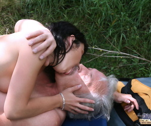 Dark haired teen pleasures an old man orally before sex in a forest clearing