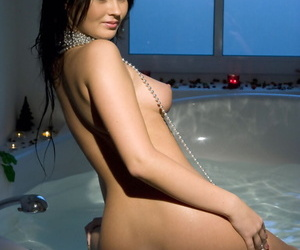 Dark haired girl Antonia sets her great tits loose while in an opulent bathtub