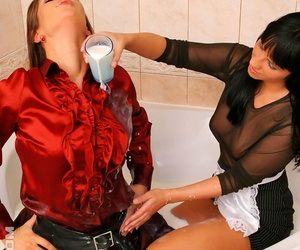 Maid bathes her clothed female employer in jugs of milk in the bath tub