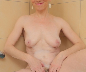 Thin older lady Dorena exposes plays with her pink pussy in the bathtub