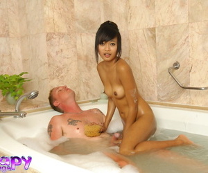 Hot young Asian teen lathers white cock for rub down & rides on zenith in non-radioactive shampoo