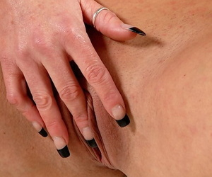 Middle aged blonde woman pets her shaved pussy with black fingernails