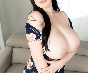 Dark haired girl Dina Sahari releases her huge tits from a dress as she strips