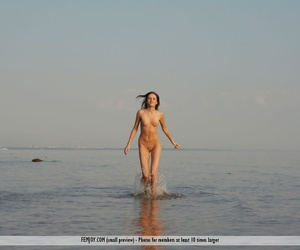 Totally naked girl Marie washes mud off her body while playing at the beach