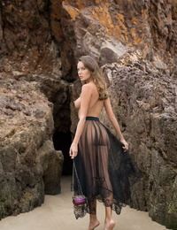 Beautiful teen Clover stands completely naked on beach sand