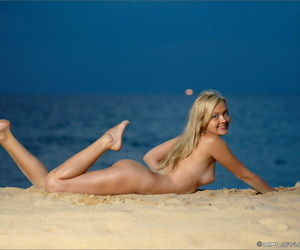 Hot blonde with nice ass gets on her knees naked in the sand at the beach