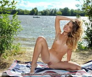 Skinny blonde Lola Krit shows off her tan lined body on waterside beach towel