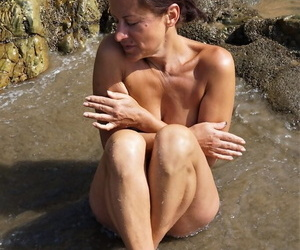 Older amateur Diana Ananta shows her tan lined body in surging waters
