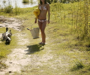 Teen solo girl Elela takes off her bikini before wading into river