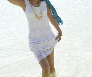 Asian girl wander into the ocean to her knees in a white dress