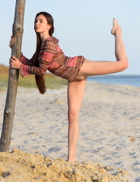 Flexible teen Lola G climbs a pole on the beach while totally naked