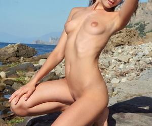 Skinny beach babe Lena flaunts her small boobs posing nude on the rocks