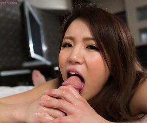 Brunette Japanese sweetie undressing before giving big dick handjob