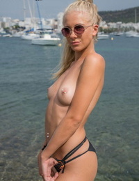 Blonde amateur shows off her pierced nipples while topless at a harbour