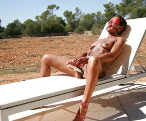 Naughty UK BDSM pornstar Lady Sarah in ball gag beside swimming pool