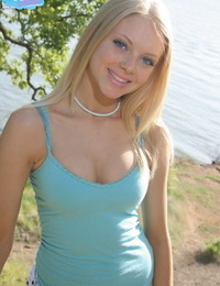 Cute blonde teen Skye Model drops her shorts lakeside to pose in white panties