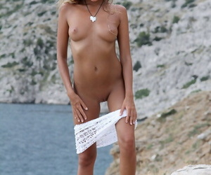 Solo sweeping Mango A modeling naked beyond rocky beach after disrobing
