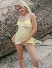 Young blonde girl exposes her lacey underwear while posing on rocks