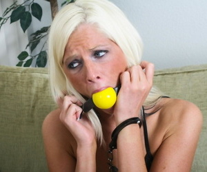 Clothed female Tricia Oaks is left struggling in cuffs and a ball gag