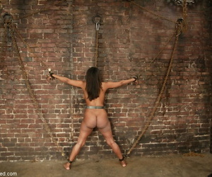 Black female Sinnamon Love has her big butt whipped while chained to a wall