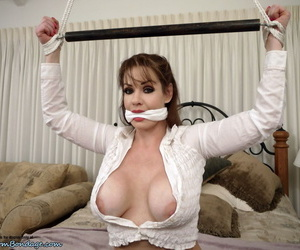 Clothed woman Alexis Taylor has her big tits exposed while tied up and gagged
