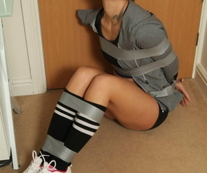 Caucasian female in Nike running shoes finds herself restrained with duct tape