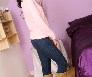 Dark haired teen Emily J removes sweater and jeans to model topless in nylons