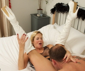 Mature blonde exchanges oral sex with her man in a mesh top and long boots
