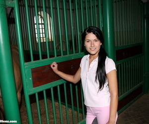 Young brunette sneaks into a horse stall to masturbate in riding attire
