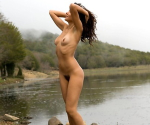 Sexy female nudist Chiara exposes her trimmed snatch by the river