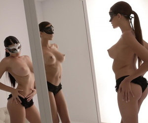 Luscious lesbian babes Silvie Deluxe and Lucy Li wear masks while using a toy