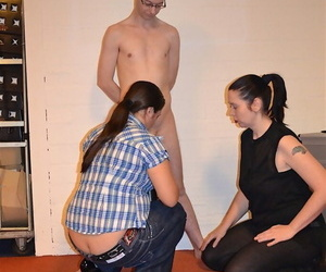 Clothed dykes force a naked male slave to suck on a strapon cock