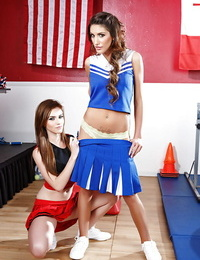Lesbian cheerleaders August Ames and Emma Stoned showing their asses